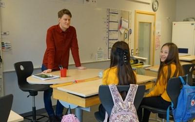 En vuxen och två barn i klassrum.