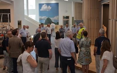 Folksamling i byggstökig hall.