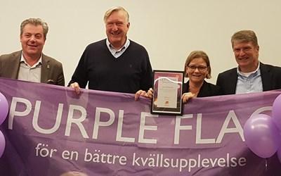 Fyra personer med en lila flagga
