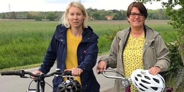 Två personer står vid sina cyklar.