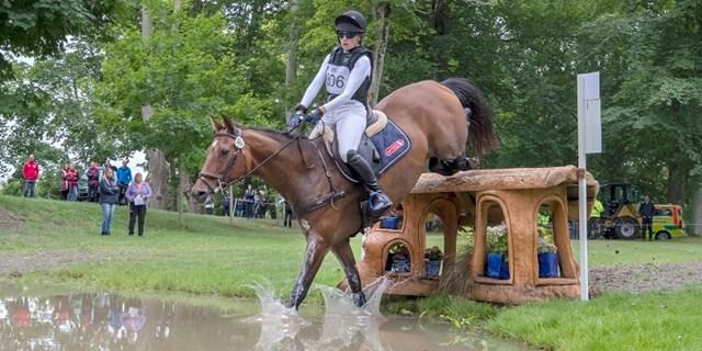 Häst och ryttare vid fälttävlandshinder med vatten.