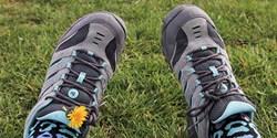 Ett par fötter i gympaskor på en grön gräsmatta.