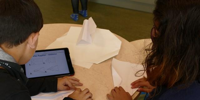 Två barn som viker pappersflygplan.