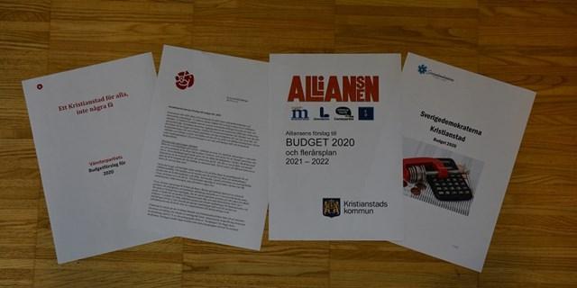 Förstasidorna på de fyra budgetförslagen.