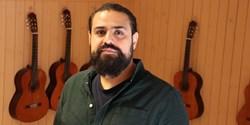 Saman som har mörkt hår och mörkt skägg står framför några gitarrer i en sal på skolan.