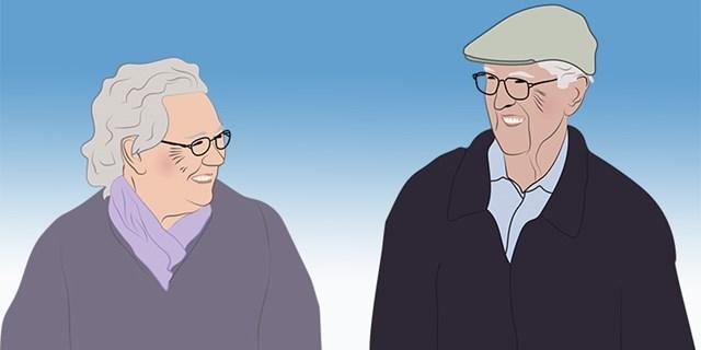 En äldre man och kvinna tittar på varandra och ler.