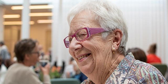 Glad äldre dam fikar på ett café.