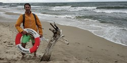 Man på strand med livboj