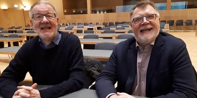 Två skäggiga herrar sitter i sessionssalen.