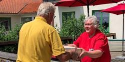 hans Vessberg räcker över tårtor till Eva Persson på Hammarshemmet.