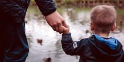 Ett litet barn håller handen med en vuxen.