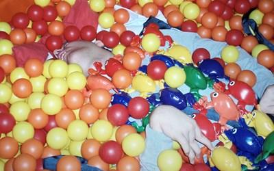 En kille som ligger i ett hav av bollar och ser ut att njuta.