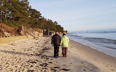 Bild på ett par som promenerar på stranden